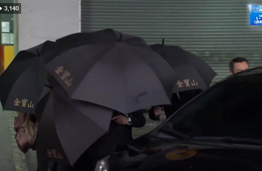 禮儀公司工作人員撐起多把黑傘,護送高以翔家屬上車。(翻攝自中時電子報臉書)