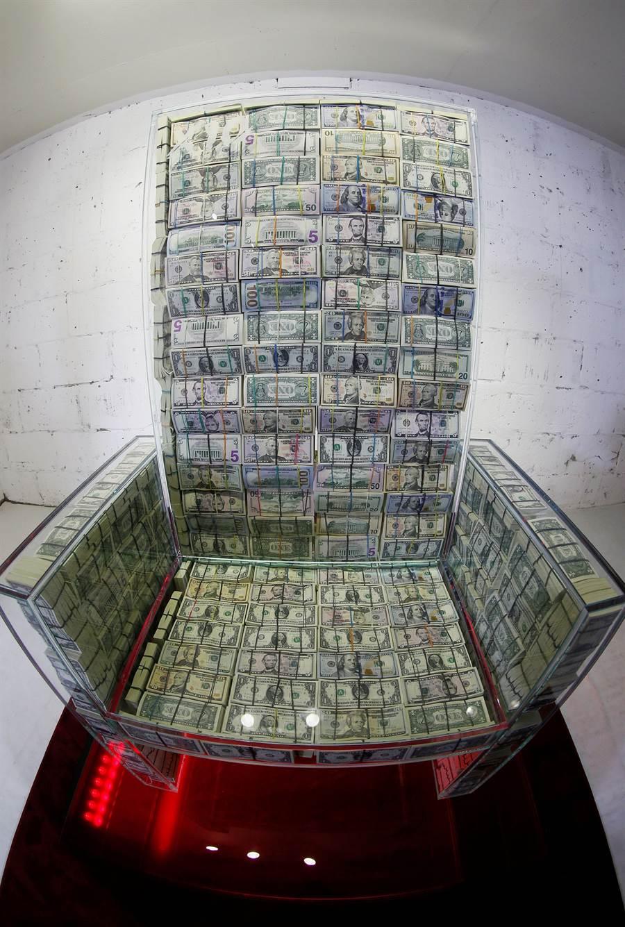 這座名為「X10金錢王座」的展品,以7厘米厚防彈玻璃製成,內部塞滿一綑綑來自不同國家的鈔票,重約半公噸。(美聯)