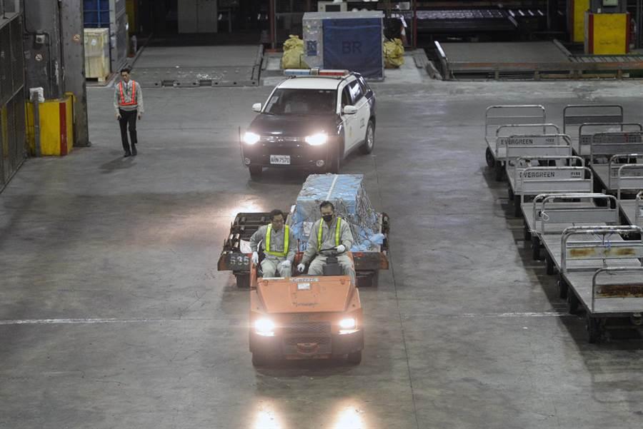 在地勤人員小心運送與警車護衛下,靈柩先送往長榮機放倉,準備驗關後移靈。(桃園記者聯誼會提供)
