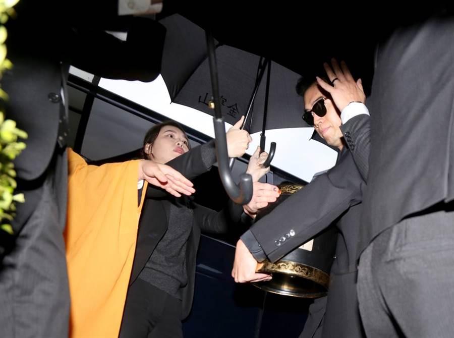 高以翔大哥撐黑傘捧牌位現身靈堂。(盧禕祺攝)