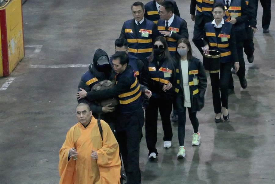 高以翔的二哥緊緊抱裝著弟弟牌位的包包,和高的女友Bella(後戴墨鏡黑色口罩者)一起返回台灣,到機場接靈的大哥上前擁抱摟肩。(粘耿豪攝)