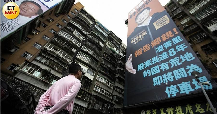 李茂基望著林昶佐懸掛的巨幅「搶政績」海報,替里長打抱不平,覺得林昶佐搶得太沒道理。(圖/黃威彬攝)