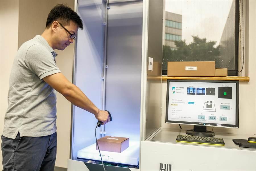 工研院開發「自動材重辨識系統」,貨物放進感測光箱,就能自動測量材積、重量並完成計價。(羅浚濱攝)