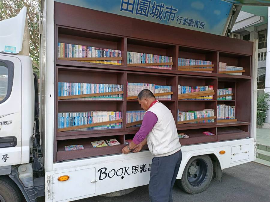 開著海區「行動圖書車」的張先生除了整理圖書車、為學童朗讀英文書,他也隨時留意學童爬梯子時的安全。(張毓翎攝)