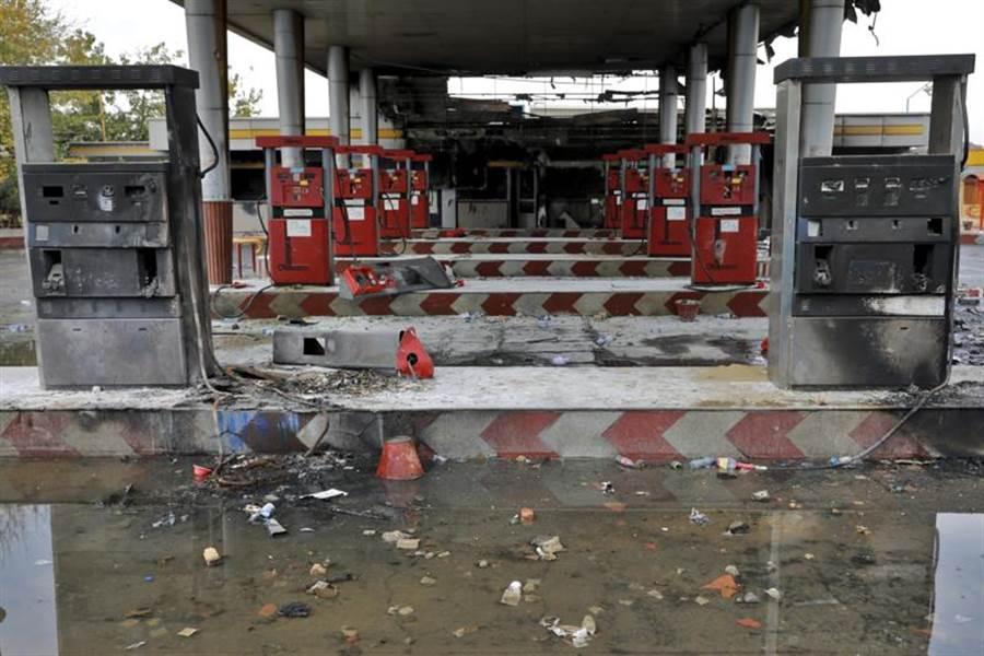 伊朗政府11月中突然宣布提高汽油價格,引發大規模群眾示威。德黑蘭一家加油站被群眾縱火搗毀,地面積滿雨水。(美聯社)