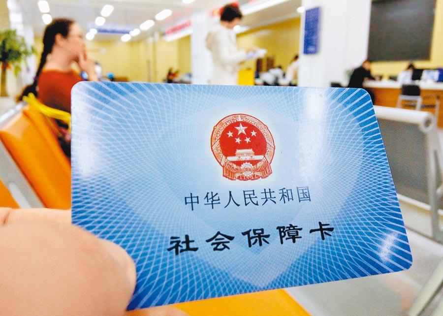 圖為福州市市民服務中心內,前來辦理社保業務的民眾展示自己的社會保障卡。(中新社)