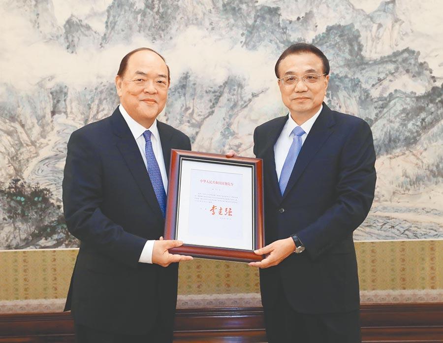 9月11日,國務院總理李克強在北京中南海紫光閣會見賀一誠,頒發任命他為中華人民共和國澳門特別行政區第五任行政長官的國務院第719號令。(新華社)