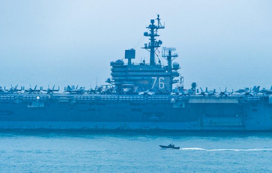 陸報復美通過香港人權法案。圖為2018年11月21日,美軍第七艦隊雷根號航空母艦停靠香港海域進行補給,一艘香港警方的快艇在航母旁行駛。(中新社)