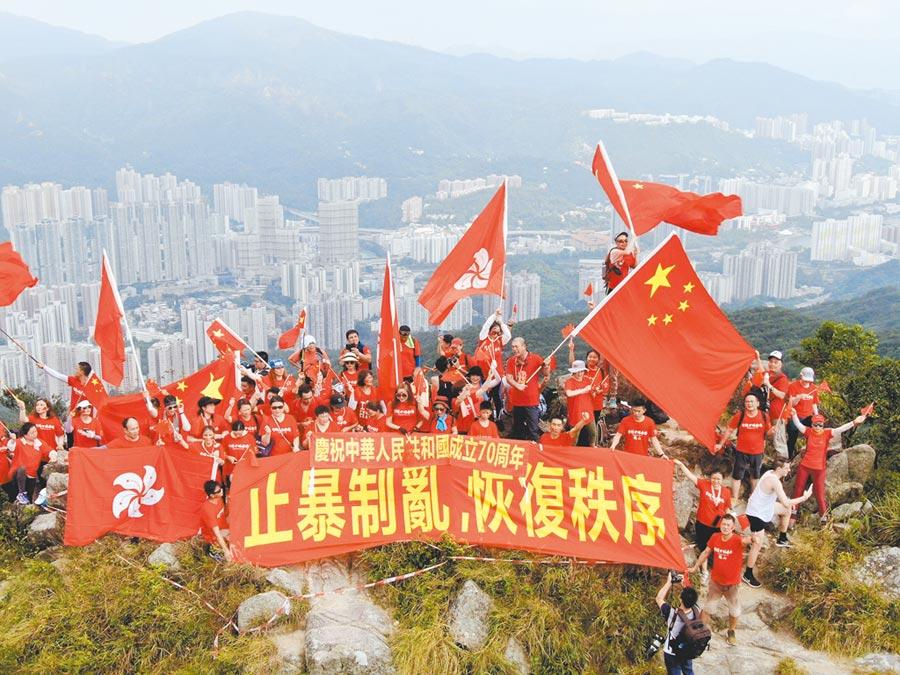 百餘名香港市民爬上獅子山頂揮舞五星旗及香港區旗,並高舉「止暴制亂,恢復秩序」標語。(新華社資料照片)