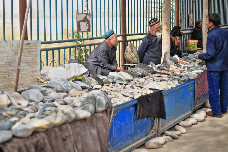 維吾爾商販在玉龍喀什河河邊的玉市販賣玉石與其他奇石,與顧客談價錢。(shutterstock)