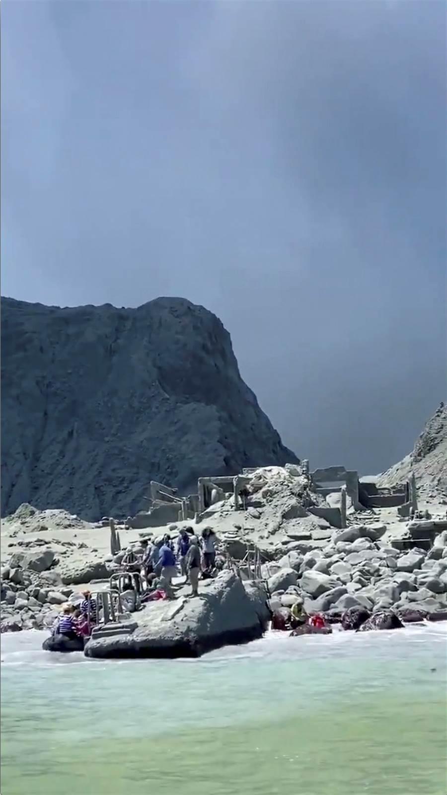 紐西蘭懷特島9日火山爆發,在島上遊覽的觀光客準備搭船離開。(圖/路透社)