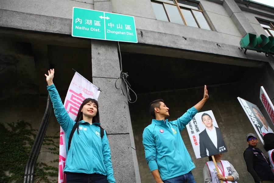 民進黨立委候選人高嘉瑜、吳怡農13日合體在堤頂大道向往來民眾拜票,不少民眾搖下車窗比讚打氣、加油。(張立勳攝)