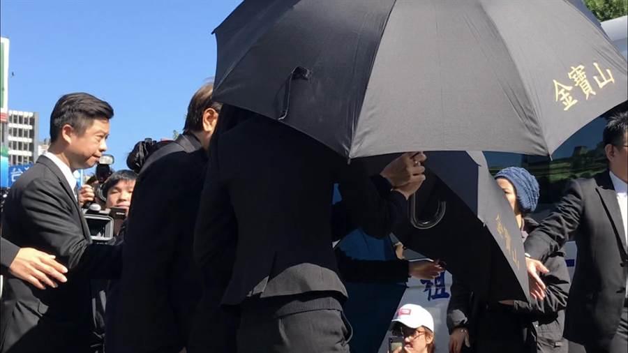 高以翔爸媽在工作人員以大黑傘遮掩下離開告別式現場。(林淑娟攝)