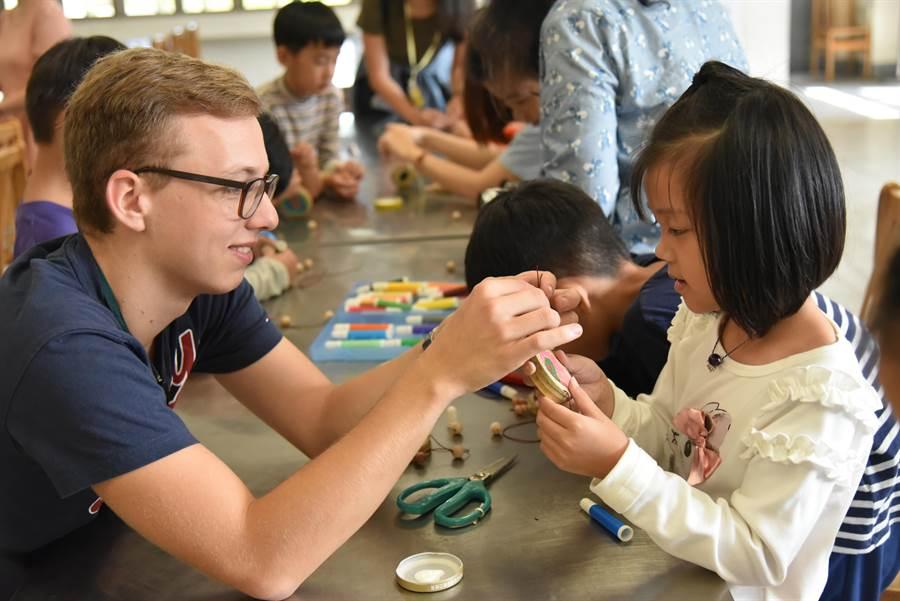 南投縣中洲國小國際學伴相見歡,大小學伴一起合力完成充滿農村兒時懷舊風的竹製波浪鼓。(教育部提供/林志成台北傳真)