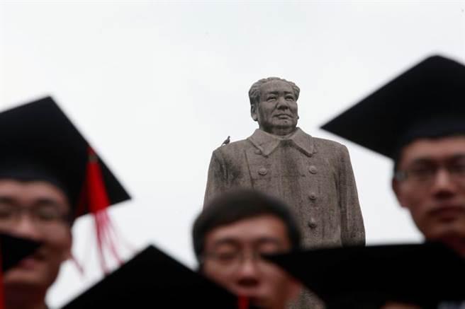 復旦大學畢業生拍畢業照,不免與毛澤東合影。(圖/路透社)