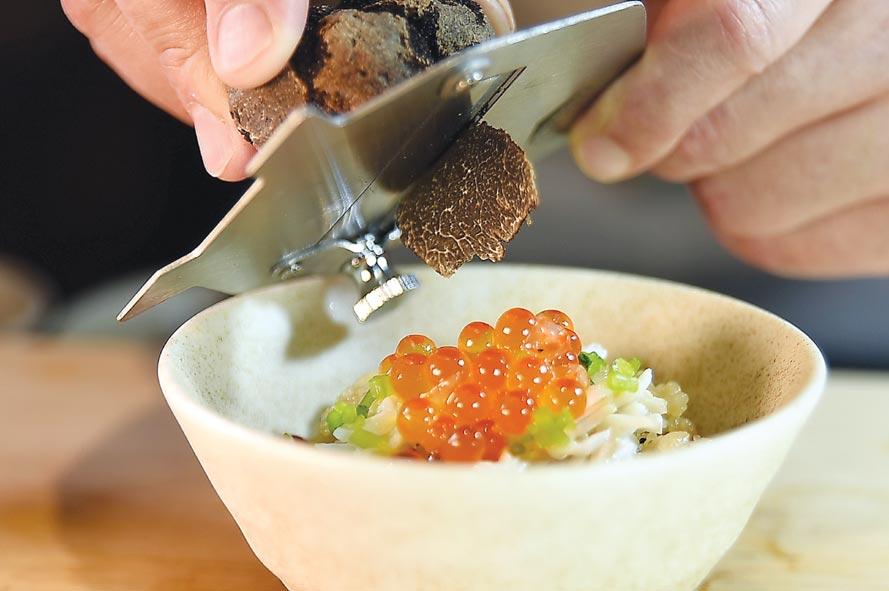 〈活體鱈場蟹黑松露土鍋飯〉是蟹肉和松露碎與米飯一起用土鍋炊煮,掀蓋後放在添盛鮭魚卵並現刨黑松露提味,味道極佳。圖/姚舜