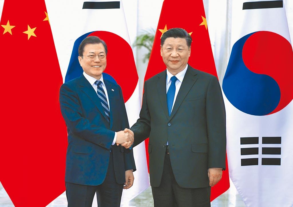 大陸國家主席習近平(右)23日在北京人民大會堂會見韓國總統文在寅。 (新華社)