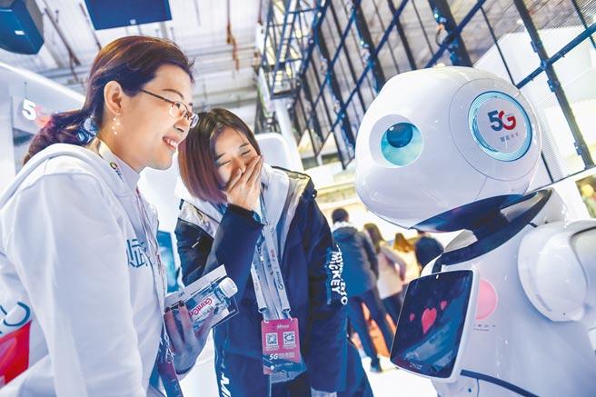 11月21日,2019世界5G大會在北京開幕,參觀者與5G機器人互動。(新華社)