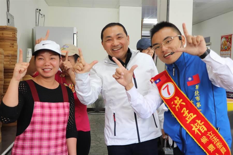 新北市長侯友宜(中)今早在市政行程前請假一小時,陪同洪孟楷(右)掃街拜票。(吳亮賢攝)