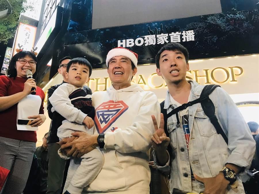 前總統馬英九平安夜到西門町,用正確抱姿抱著小孩,展現親民功力。(張穎齊攝)