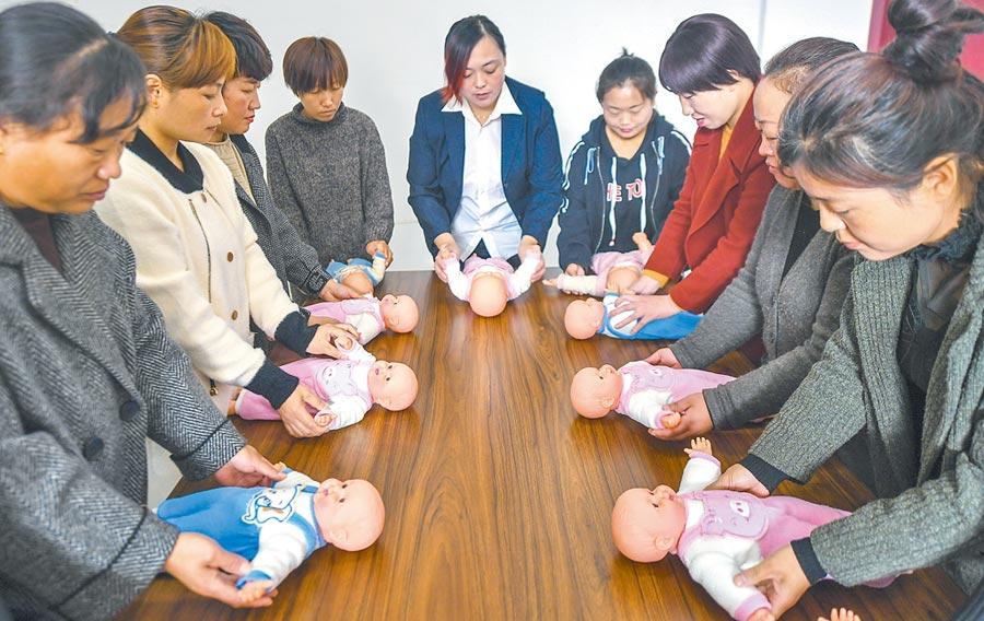 大陸對家政服務需求與日俱增,圖為家政老師在河北省武強縣就業培訓中心指導學員做「嬰兒被動操」。(新華社資料照片)