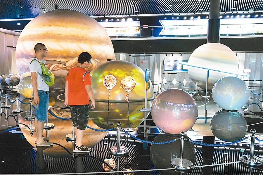 7月24日,遊客帶著孩子在貴州平塘國際天文體驗館參觀「太陽系家族」。(新華社)