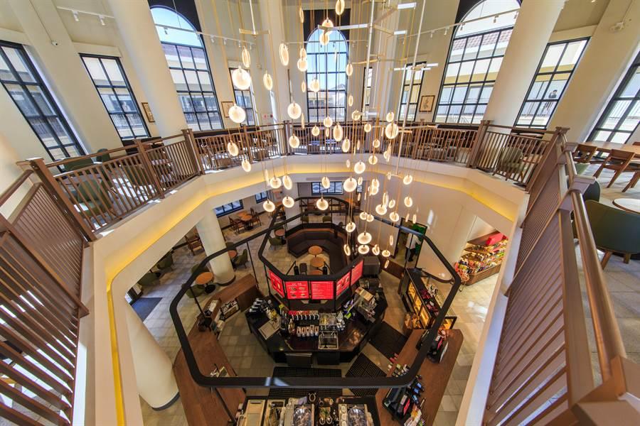 星巴克麗寶鐘樓門市,以獨特的八角形建築,門市室內特別設計以多邊形中島吧檯,並將天花挑高17米,照映吧檯上方錯落垂降的五組造型吊燈,雍容有致。(圖/品牌提供)