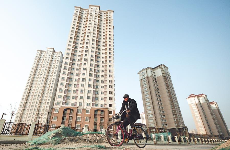 大陸房產租賃行情下跌,圖為行人騎車從天津一處公租房住宅小區前走過。(中新社資料照片)