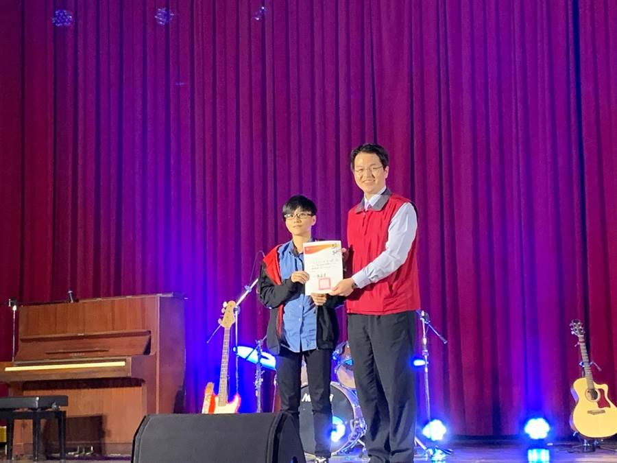 三年級的王嬿筑(左)以「往日情」拿下獨唱組的第一名,校長張正彥(右)頒發獎狀。(暨大附中提供/張晉銘南投傳真)