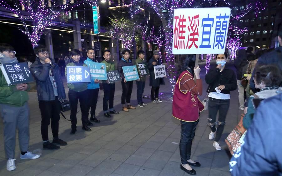 民進黨青年部與宜蘭在地青年團體27日晚間在台北市政府轉運站上車月台外,為呼籲宜蘭青年返鄉投票,向排隊搭車返鄉的旅客進行宣導,提醒旅客明年1月11日要去投票。