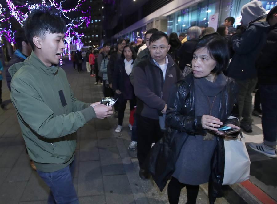 民進黨青年部與宜蘭在地青年團體向排隊搭車返鄉的旅客進行宣導,並發放由「傑尼龜」與「龜山島」為意象,所發想的「接你龜」貼紙。(鄭任南攝)