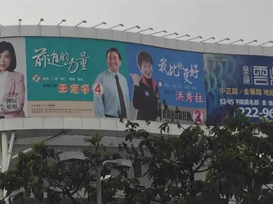 國民黨第六選區立委候選人洪秀柱一幅「我比他更好」大型看板,一旁看板則是對手民進黨立委王定宇。(曹婷婷攝)