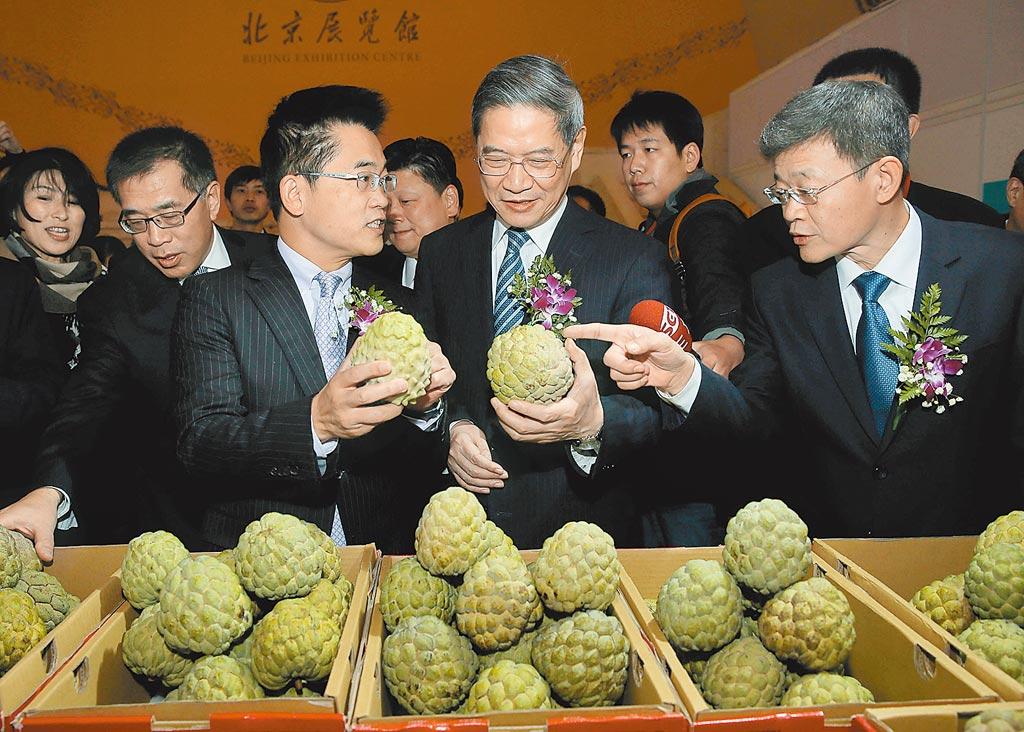2016年底,台灣8縣市農特產品展銷暨旅遊推介洽談會在北京開幕,時任台東縣長黃健庭(左)與國台辦主任張志軍(中)在觀賞台灣釋迦。 (新華社)