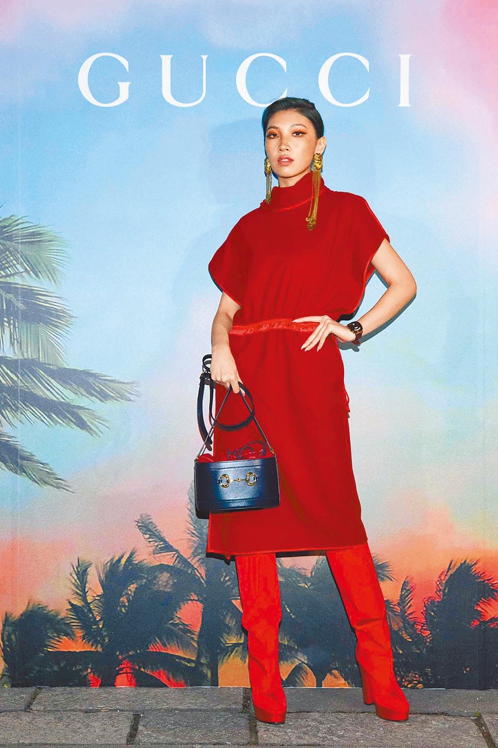 Karencici一身紅,難得女人味。酒紅色羊毛絨無袖高領洋裝10萬5000元,櫻桃紅高跟馬靴4萬3200元,紅藍撞色皮革水桶包6萬7500元。(GUCCI提供)