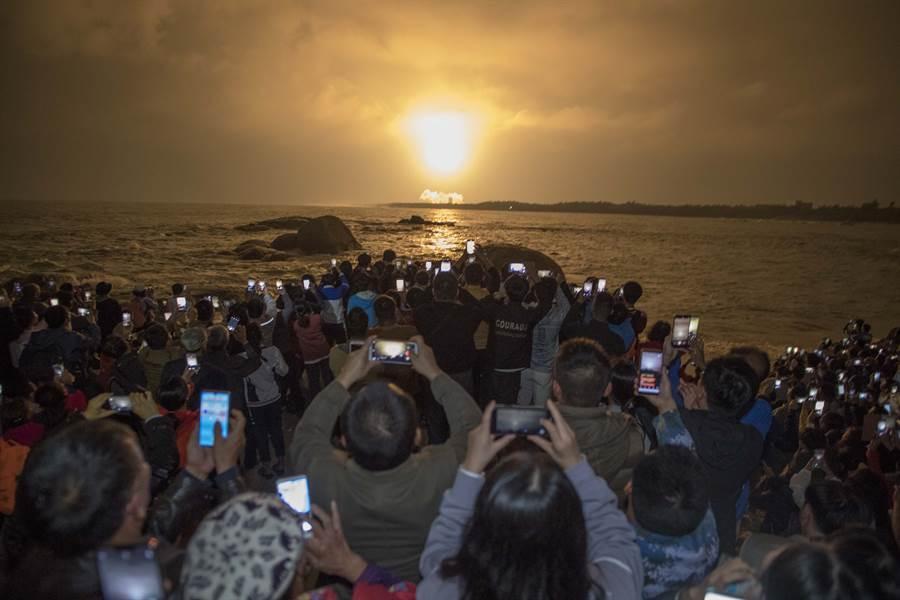 大陸長征5號火箭在時隔兩年多後的第3次發射。圖為海南省文昌市龍樓鎮淇水灣,民眾聚集觀看長征5號火箭發射,紛紛拿起手機拍照。(圖/中新社)