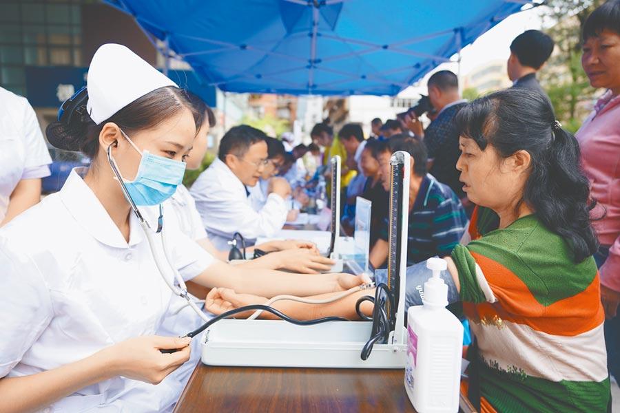 高血壓是導致腦中風的最重要因素,每日最好測1次血壓,圖為醫護人員為市民測量血壓。(新華社資料照片)