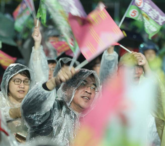 熱情支持者身穿雨衣為阮昭雄搖旗吶喊。(陳怡誠攝)