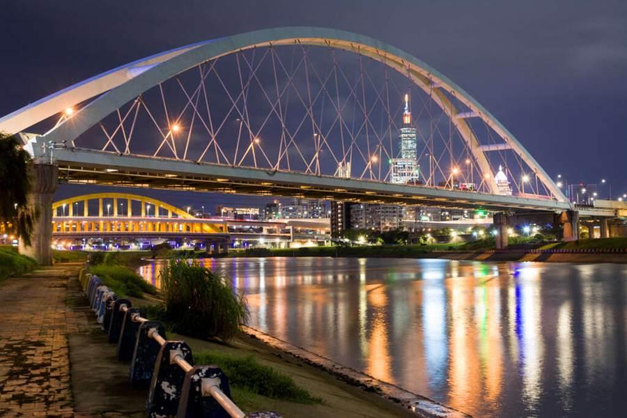 以101大樓及台北城市閃爍的燈光為背景,搭配上倒映在河面的橋景,也是令人炫目的構圖。(圖取自台北旅遊網)