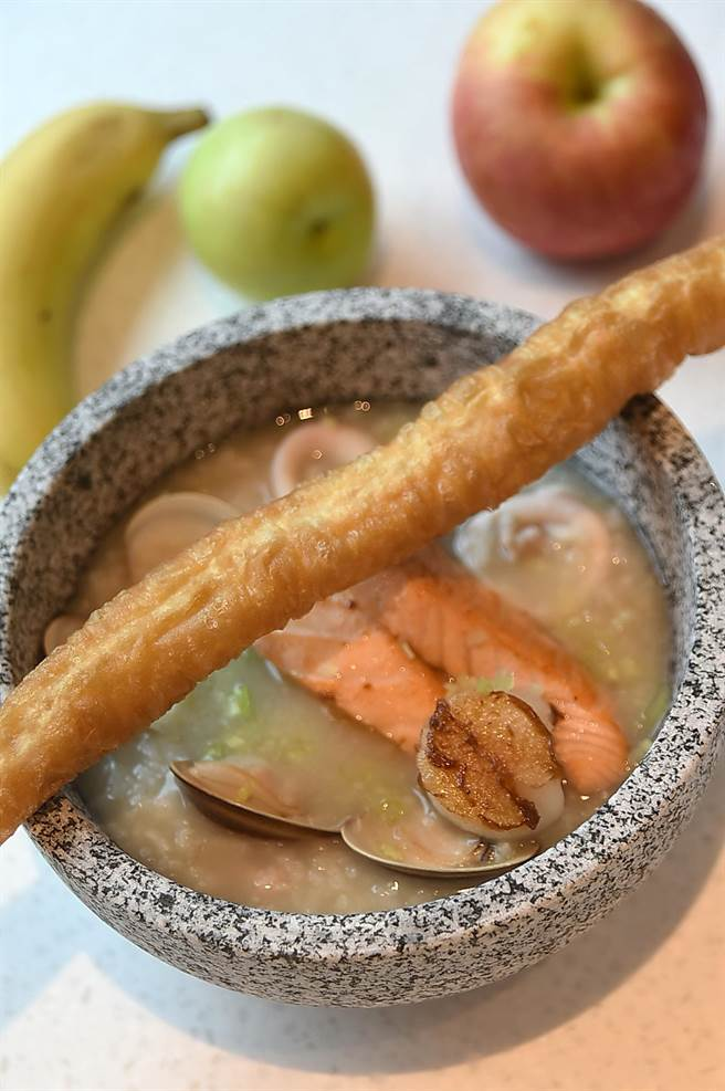 大直英迪格酒店早餐提供的〈海鮮粥〉,粥內有蛤蜊、透抽,還有大塊的煎烤鮭魚,內容非常豐富。(圖/姚舜)