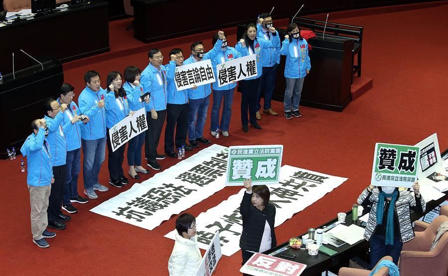 立法院31日院會三讀通過「反滲透法」草案,國民黨立委在議場內舉起標語,抗議此案侵害人權、侵害言論自由。(姚志平攝)