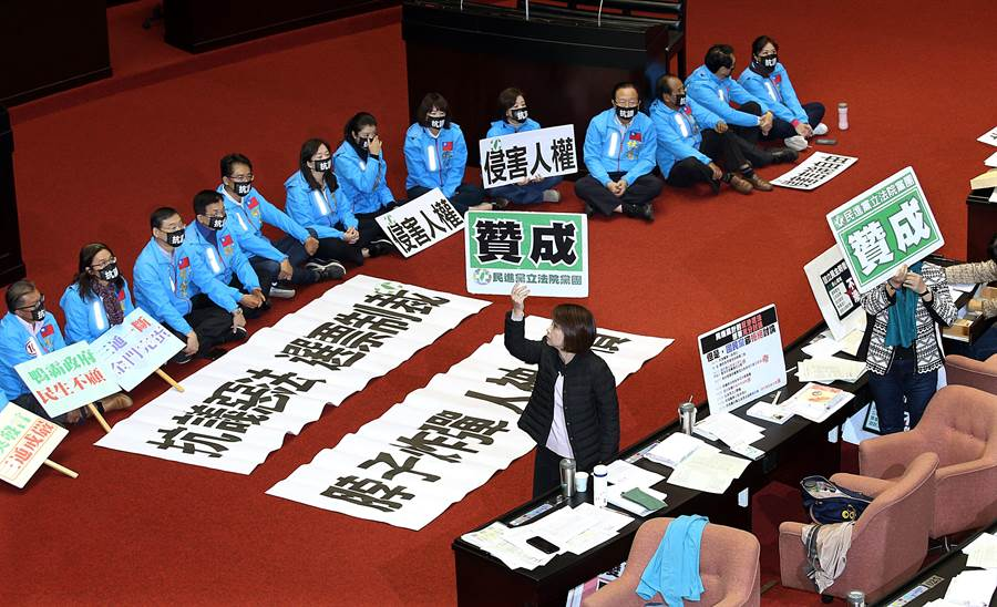 立法院31日院會處理「反滲透法」草案,國民黨立委拉起布條,戴著口罩在議場內靜坐,抗議此法案侵害人權,民進黨團在逐條表決中舉出贊成牌子,以人數優勢強行通過。(姚志平攝)