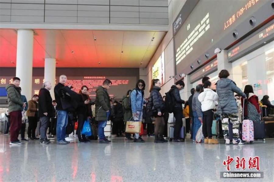 陸春節假期估4.5億人次出遊。圖為民眾在高鐵站排隊取票。(照片取自中新網)