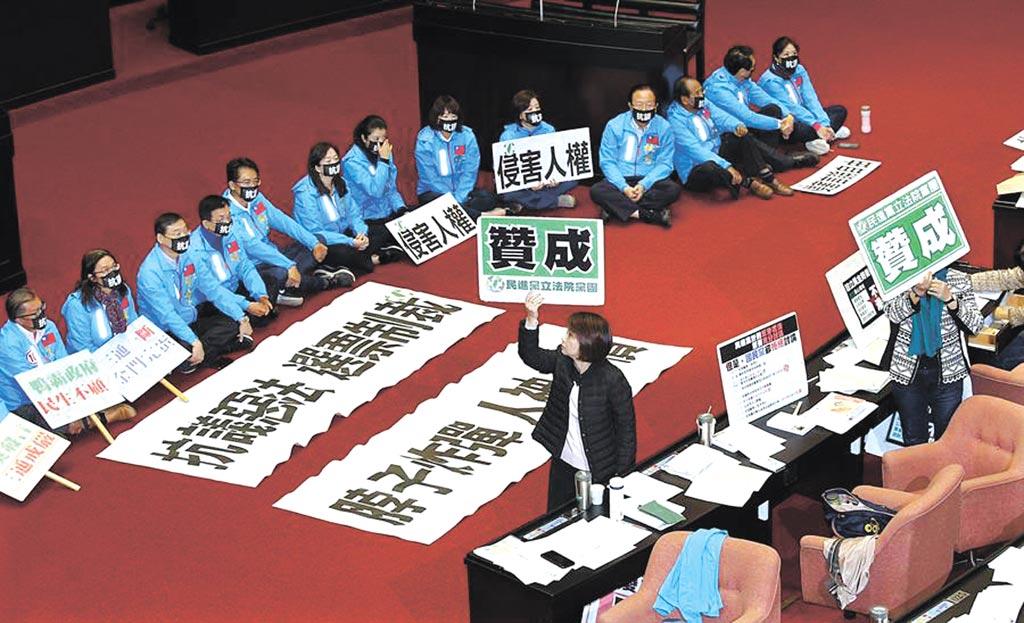 立法院2019年12月31日院會處理「反滲透法」草案,國民黨立委拉起布條,戴著口罩在議場內靜坐,抗議此法案侵害人權,民進黨團在逐條表決中舉出贊成牌子,以人數優勢強行通過。(姚志平攝)