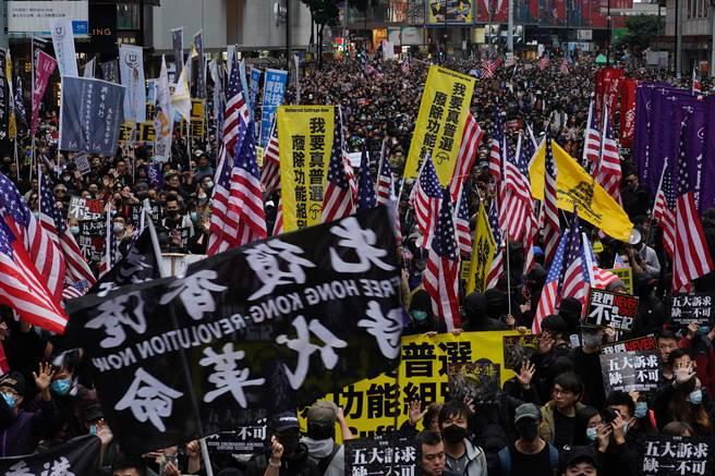 香港反送中運動於2020元旦就開始示威,下午在維多利亞公園由民陣舉行的遊行活動至少聚集了萬人以上,群眾舉著英美國旗與標語口號遊行。(圖/美聯社)