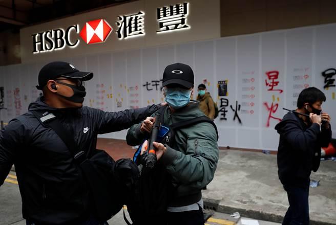元旦下午遊行的示威者破壞了匯豐銀行的設施,警方發射鎮暴槍,並逮捕5名示威者。(圖/路透)