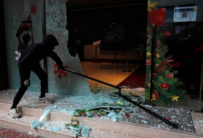 匯豐銀行雖然架起木板防護,但仍遭示威者破壞,玻璃門窗亦被砸毀。警方已逮捕數名破壞者。(圖/路透)