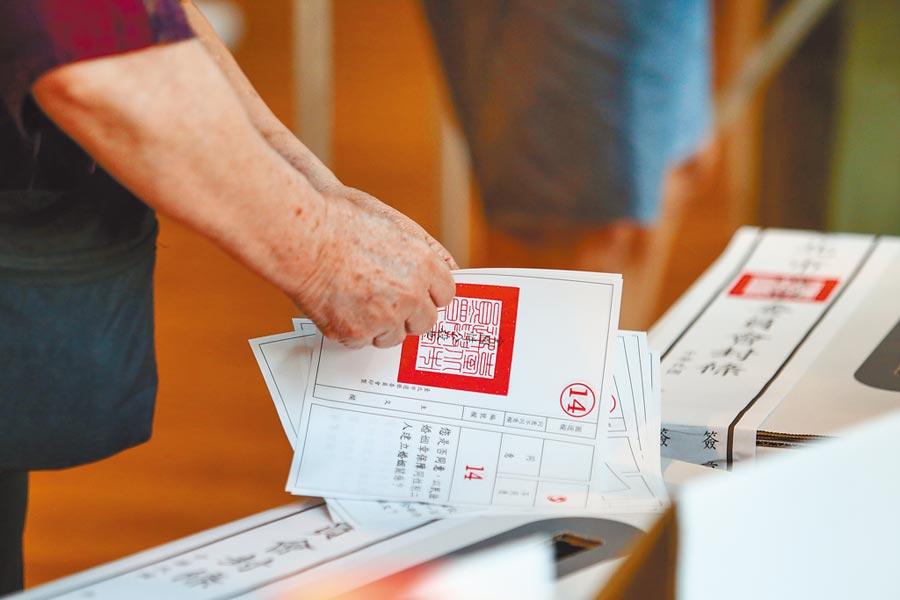 2018年11月24日,民眾在九合一選舉合併10案公投將選票投至票箱。(本報系資料照片)