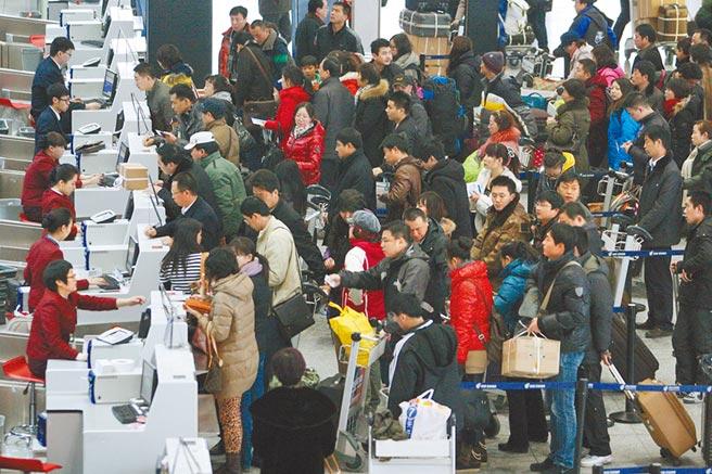 旅客在北京首都機場航站樓等候辦理乘機手續。(新華社資料照片)