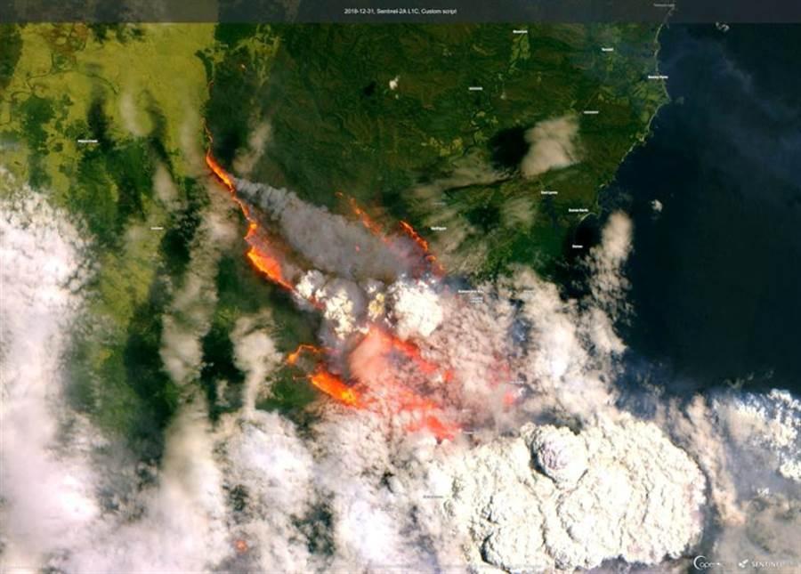31日衛星照片顯示,澳洲新南威爾斯省巴特曼斯貝冒起火光與白煙。(路透)