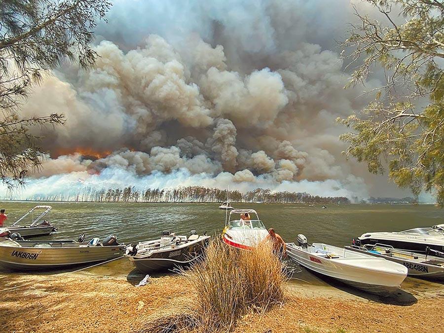 澳洲林火肆虐,部分地區天空被濃煙所籠罩,新南威爾斯當局要求遊客2天內撤離。圖為從遠處看位於新南威爾斯的康喬拉湖濃煙直上雲霄的恐怖景象。(美聯社)